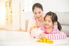 Enfant de fille mettant l'argent dans la tirelire Photos stock