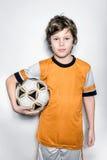 Enfant de footballeur dans l'uniforme orange avec la boule Photo stock