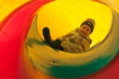 Enfant de garçon dans la glissière de tube Photo stock