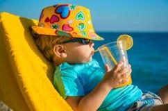 Enfant de garçon dans le fauteuil avec le verre de jus sur la plage Photos stock