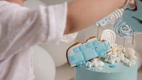 Enfant de garçon de deux ans mangeant un gâteau bleu de fête avec une voiture clips vidéos