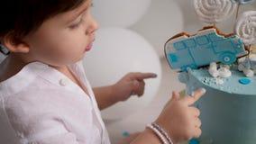 Enfant de garçon de deux ans mangeant un gâteau bleu de fête avec une voiture banque de vidéos