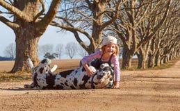 Enfant de jeune fille jouant avec son chien great dane Image stock