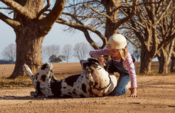 Enfant de jeune fille jouant avec son chien great dane Image libre de droits