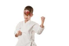 Enfant de karaté avec la peinture rouge de visage de gragon Photographie stock libre de droits