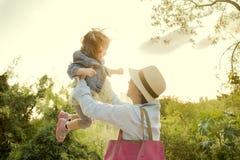 Enfant de levage de femme  Photographie stock
