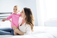 Enfant de mère et de bébé sur un lit blanc Photos libres de droits