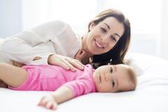 Enfant de mère et de bébé sur un lit blanc Photo stock