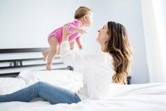 Enfant de mère et de bébé sur un lit blanc Images libres de droits