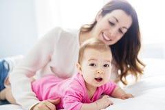 Enfant de mère et de bébé sur un lit blanc Image stock