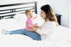 Enfant de mère et de bébé sur un lit blanc Photos stock