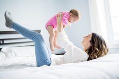 Enfant de mère et de bébé sur un lit blanc Image libre de droits