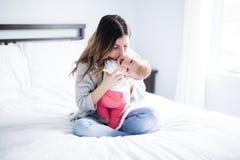 Enfant de mère et de bébé sur un lit blanc Photographie stock