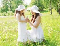 Enfant de mère heureuse et de petite fille utilisant un chapeau de paille avec des pissenlits Image libre de droits