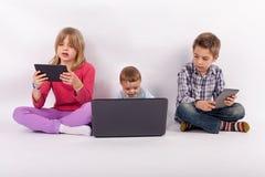 Enfant de mêmes parents à l'aide des comprimés et de l'ordinateur portable photos stock
