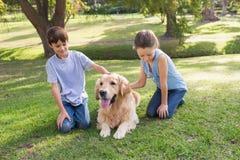 Enfant de mêmes parents avec leur chien en parc Image libre de droits