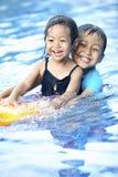 Enfant de mêmes parents ayant l'amusement à la piscine Photographie stock libre de droits