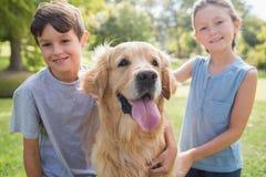 Enfant de mêmes parents de sourire avec leur chien en parc Photographie stock libre de droits