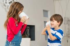 Enfant de mêmes parents jouant avec Tin Can Phone photographie stock