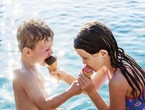 Enfant de mêmes parents partageant la crème glacée par la piscine Images libres de droits