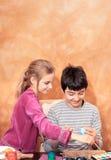 Enfant de mêmes parents peignant des oeufs de pâques à la table Photos libres de droits