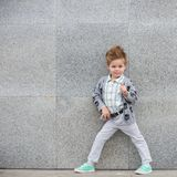 Enfant de mode posant près du mur gris Photos stock