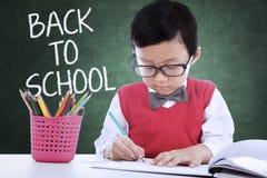 Enfant de nouveau à l'école et dessin dans la classe Image stock