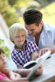 Enfant de père et de garçon lisant un livre Photo libre de droits