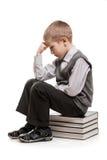 Enfant de penseur s'asseyant sur des livres de relevé photo stock