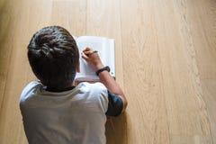 Enfant de petit garçon lisant un livre Il se trouve sur le plancher Photo libre de droits