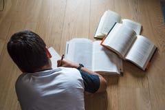 Enfant de petit garçon lisant un livre Il se trouve sur le plancher Photographie stock