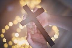 Enfant de petit garçon priant et tenant le crucifix en bois Photographie stock libre de droits