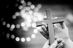 Enfant de petit garçon priant et tenant le crucifix en bois Images libres de droits