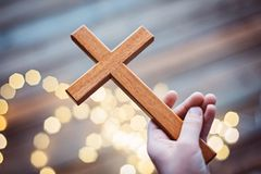 Enfant de petit garçon priant et tenant le crucifix en bois Photos stock