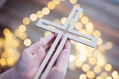 Enfant de petit garçon priant et tenant le crucifix en bois Photo stock