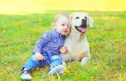 Enfant de petit garçon s'asseyant avec le chien de golden retriever photos stock