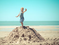 Enfant de petit garçon se tenant sur une colline sur la plage avec ses bras photos stock
