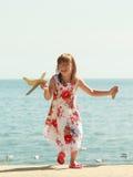 Enfant de petite fille à la plage avec l'avion plat de papier Photographie stock libre de droits