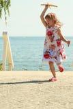 Enfant de petite fille à la plage avec l'avion plat de papier Photos libres de droits
