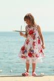 Enfant de petite fille à la plage avec l'avion plat de papier Photo stock