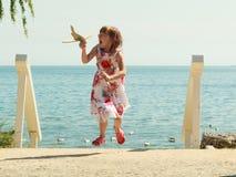 Enfant de petite fille à la plage avec l'avion plat de papier Photo libre de droits