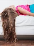 Enfant de petite fille avec de longs cheveux à l'envers sur le sofa Photo stock