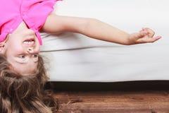 Enfant de petite fille avec de longs cheveux à l'envers sur le sofa Images libres de droits