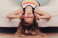 Enfant de petite fille avec de longs cheveux à l'envers sur le sofa Image stock