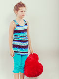 Enfant de petite fille avec l'oreiller rouge de forme de coeur Image libre de droits