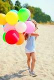 Enfant de petite fille avec les ballons colorés sur la plage Photo libre de droits