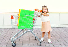 Enfant de petite fille et chariot heureux de chariot avec les paniers colorés dans la ville Images stock