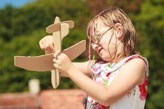 Enfant de petite fille extérieur avec l'avion plat de papier Photographie stock libre de droits