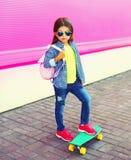 Enfant de petite fille de mode avec la planche à roulettes, sac à dos dans la ville sur le mur rose coloré image libre de droits