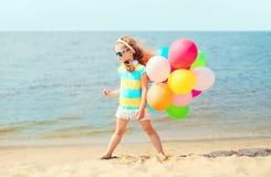Enfant de petite fille sur la plage d'été jouant avec les ballons colorés Image libre de droits